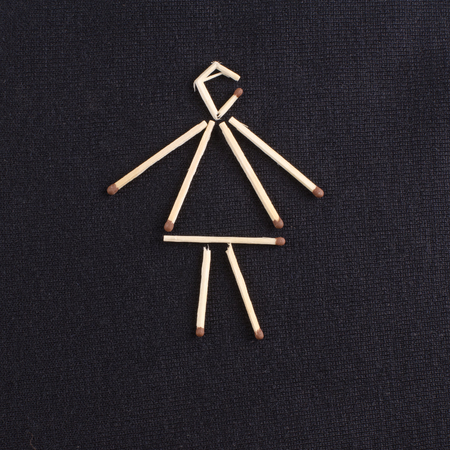 simplification: a female figure laid out matchsticks on a dark knitted surface Stock Photo