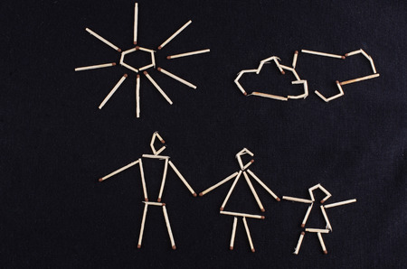 love strategy: male and female figures and a child laid out matchsticks on a dark knitted surface Stock Photo