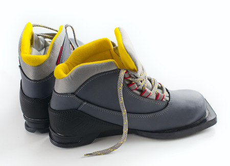 ski track: Black and gray ski boots with yellow trim on light background Stock Photo