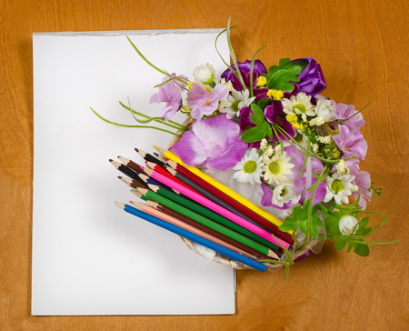 creative arts: colored pencils lie in a wicker vase with flowers. Near white sheet of paper Stock Photo