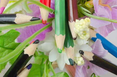 paper arts and crafts: colored pencils for drawing on the background of the bouquet of artificial flowers Stock Photo
