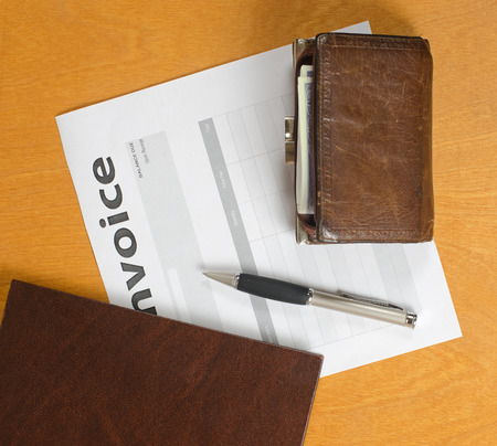 invoices: blank invoices and old leather and fountain pen lying on a light wooden surface.