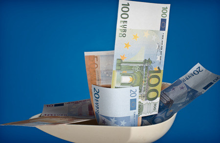 passed out: Euro banknotes passed through a meat grinder. Out of the grinder dollars.
