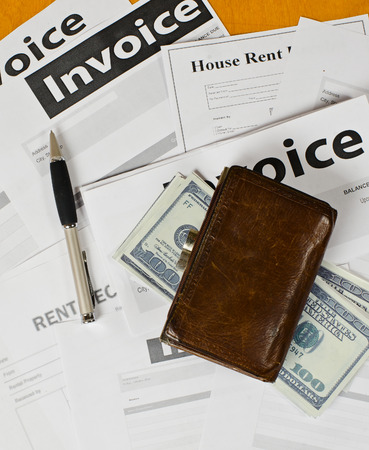 tree service business: many paper invoices lying on a wooden surface. They are the fountain pen a few dollar bills and old leather purse Stock Photo