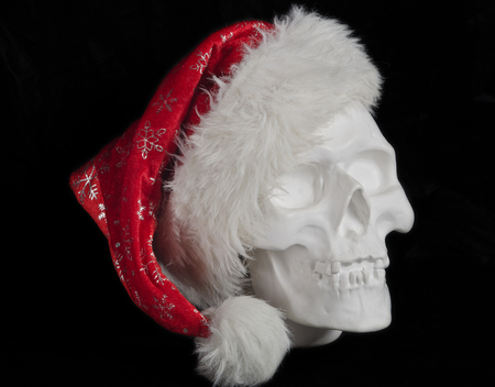 white imitation of a human head (skull) in Santa Claus hat, photographed on a black background