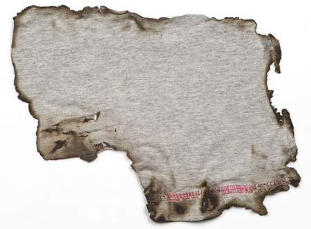 old linen fabric, with burnt edges on white surface. Fabric with bright texture