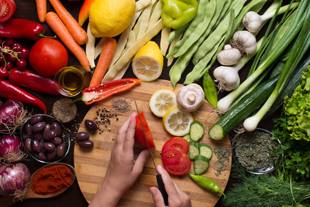 directly above: Photo from directly above of human hands slicing vegetables and variation of different autumn vegetables and spices around