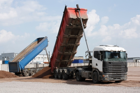 multi-ton dump truck unloads sand on  construction site photo