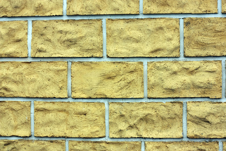 facing a wall: the  yellow facing tiles on cement wall as texture