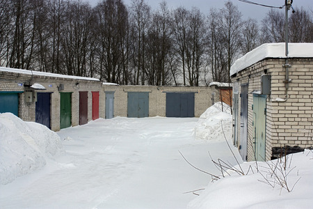 warehouse building: brick warehouse building with  closed red, green, blue, gray metal  doors on a background of trees.large snow drifts, the roof in the snow.Clear winter day. Stock Photo