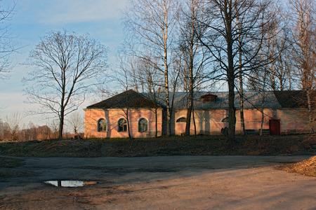 roze huis staat op een heuvel aan sunset.Around het huis grote bomen zonder leaves.In de voorgrond, een kleine plas water.Blue hemel, de schaduwen van de bomen op de muur. Dit is een van de gebouwen van het Instituut voor Fysiologie Pavlov Koltushi, Lening