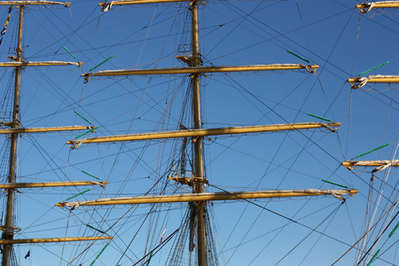 topsail: three masts and tall sail ship  ropes over blue sky.In the center is mainmast. On the left mizzenmast.On the right foremast.