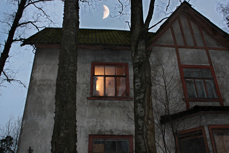 two floors: Old house with two floors with a light in the window and the moon in the evening sky.