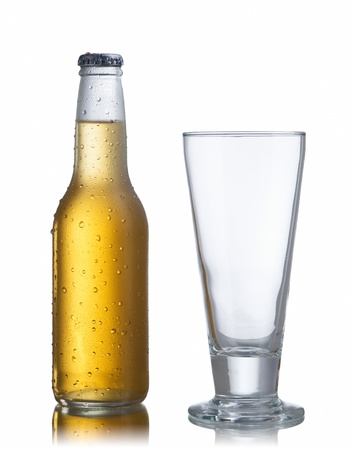 glass of beer: Non-glossy white beer bottle, back lighted showing a glowing golden beer content, drops and condensation and an empty glass