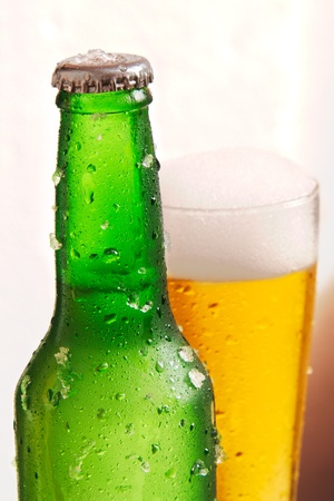Green bottle of beer in front with drops and chips of ice with a glass of beer in the back with drops and froth Stock Photo