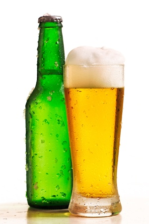 Glass of beer in the front with drops and froth with green bottle of beer in the back with drops and chips of ice Stock Photo - 9404974