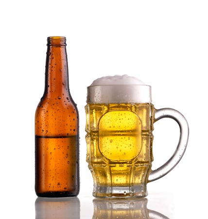 froth: Mug of beer with froth and an open half filled brown bottle of beer, both showing condensation and droplets Stock Photo