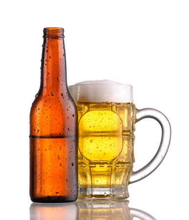 Mug of beer with froth behind an open half filled brown bottle of beer, both showing condensation and droplets Stock Photo - 9413588