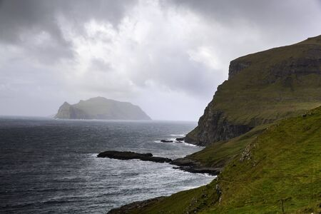 Mykines island on the horizon a view from Bøur village, Vagar, Faroe Islands Stock Photo