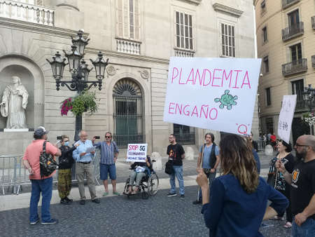 Barcelona, Spain - 20 June 2020: Manifestation against 5g and covid vaccination on Sant Jaume Square, a woman holding slogan saying fake pandemic
