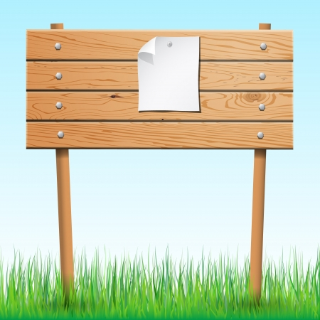 Wooden sign with paper sheet on green grass   photo