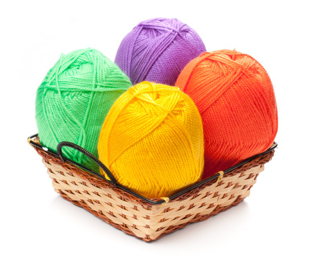 four yarn skeins in yellow, orange, green, purple colors in basket on white background photo