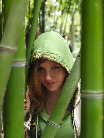 Young pretty woman walking in the park in the overgrowth of bamboo photo