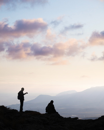 A couple meeting the sunset on the top of the mountain photo