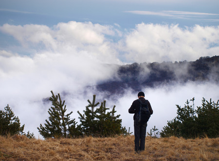 eminence: Man standing on a high mountain Stock Photo