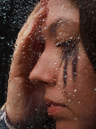 A girl is thinking standind behind the glass on one of rainy days photo
