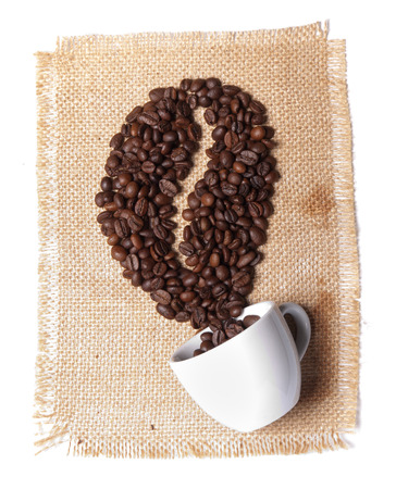 white cup with coffee beans on burlap background photo