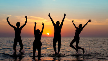 silhouette of jumping people on sunset background Stock Photo