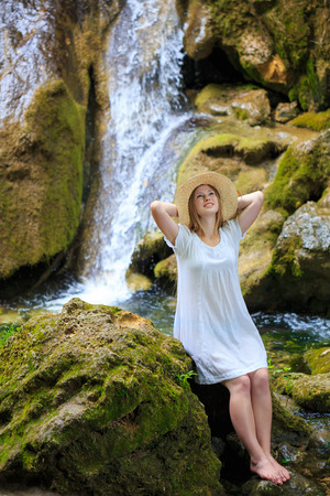 Beautiful young woman in white sundress and straw hat stopped to rest and dream near the waterfall among the mossy stones photo