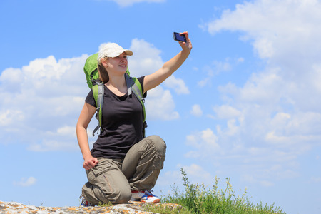 Woman with backpack take a picture of herself on top of mountain at cloudscape background photo