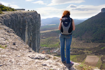 A girl standing on the edge of the high mountain and looking ahead photo