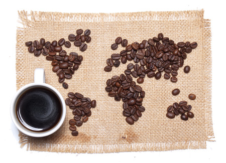 Coffee map on hessian background with white cup photo