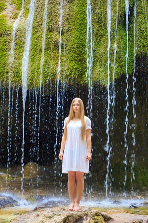 Beautiful young long-haired woman in white sundress stands barefoot on the background of a waterfall. Crimean waterfall 'Silver strings'. photo
