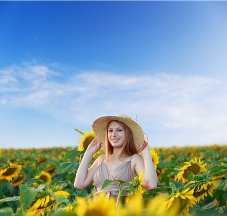 Beautiful young woman on the sunflower field in dress and straw hat with happy smile photo