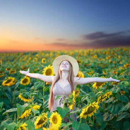 入札の美しい少女向日葵畑の夜明けを満たしています。 写真素材