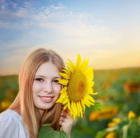 Young beautiful smiling woman with sunflower in hand on the flower field photo