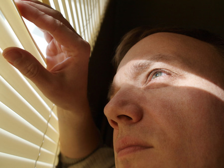 Man looking through blinds photo