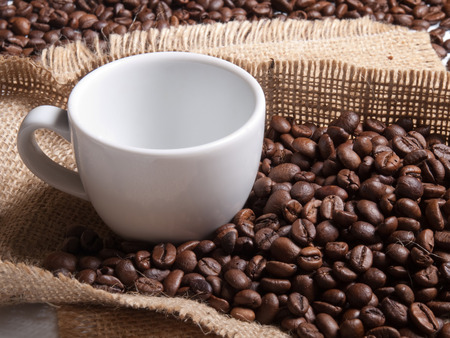 invigorate: white cup with coffee on burlap background with beans Stock Photo