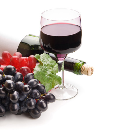 Glass of black wine and grapes on white background photo