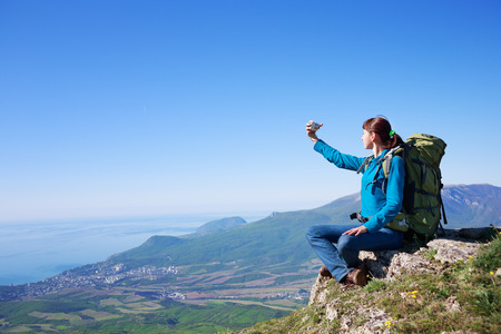 selfy: Happy young female traveller with backpack sitting at the edge of cliff at mountain landscape background in sunny summer day under blue cloudy sky with camera in hands and making selfy photo