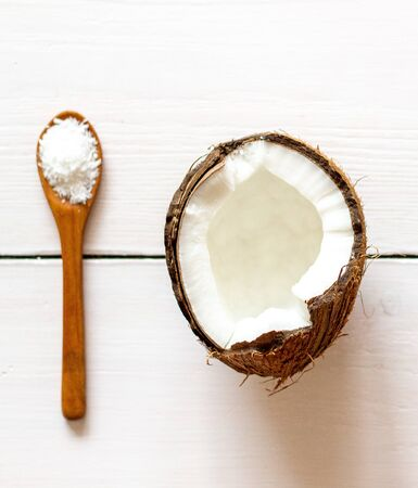 Coconut and spoon on a white wooden backdrop