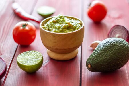 Guacamole and ingredients. Red background. Mexican cuisine