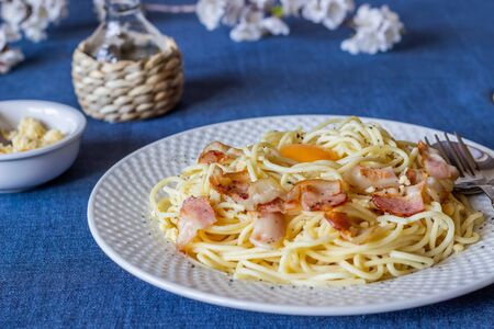 Pasta Carbonara. Flowers in the background. Italian food