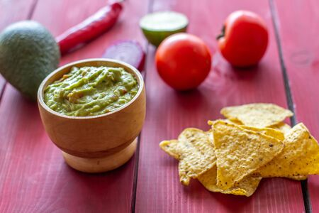 Guacamole and chips nachos. Red background. Mexican cuisine