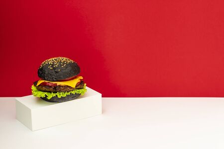 A burger on a white stand. Red and white background. Minimalism. Creative food. Restaurant design Stock Photo