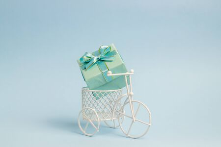 A toy bike carries a gift. The idea for a postcard. Blue background. Minimalism.